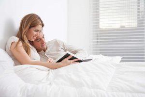 Une femme et un homme en train de lire au lit